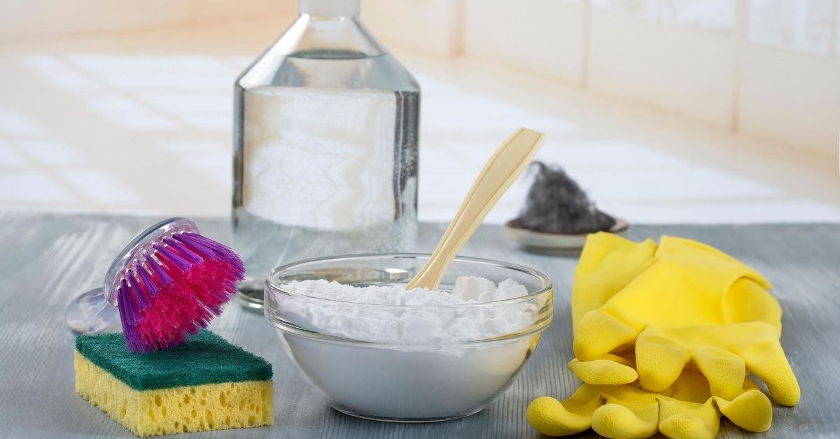 Bicarbonate of soda in a glass bowl with marigold gloves and scrubbing brushes ready for cleaning - Clean and Tidy Living