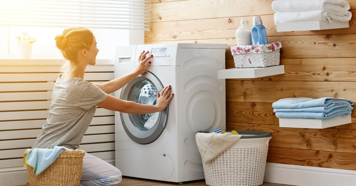 Woman closing a Washing Machine under £300 in a laundry room