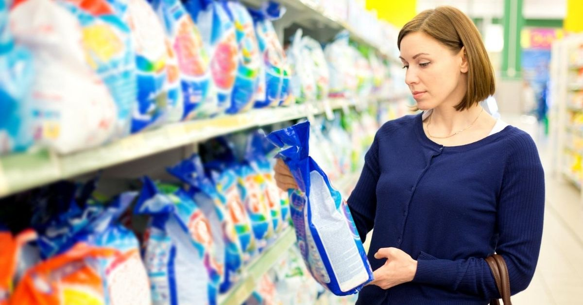 Woman holding a bag of natural washing powder in a supermarket - Clean and Tidy Living
