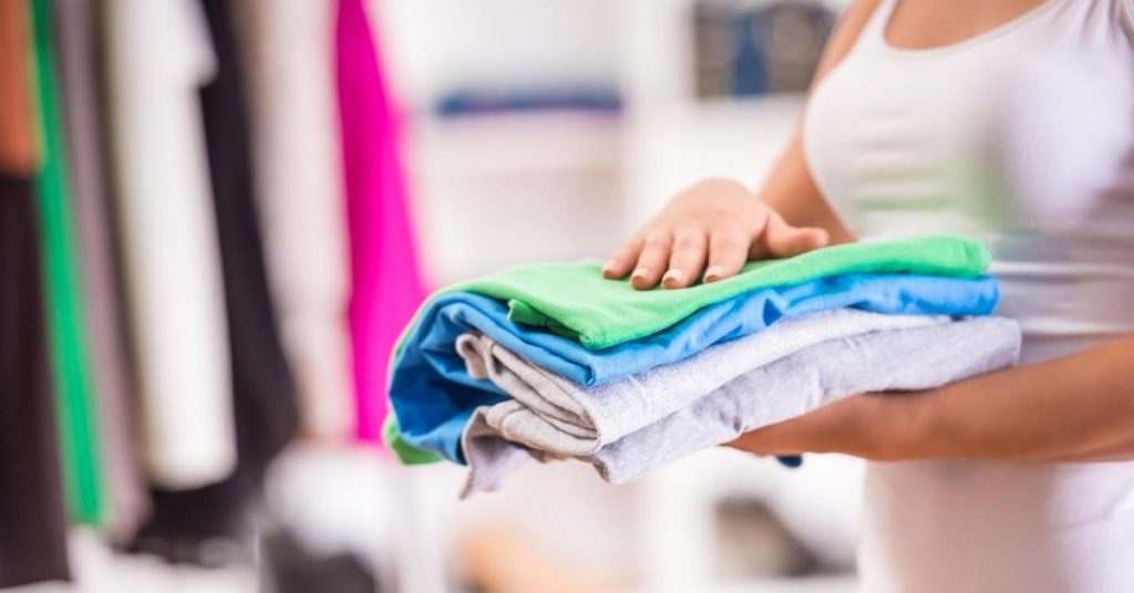 Woman holding folded clothes in hand - Tidy wardrobe