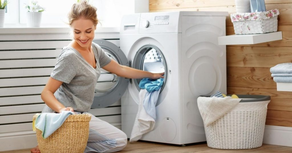 Woman putting clothes into a Washing Machine under £300 in a laundry room