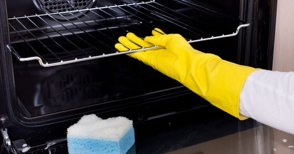 Cleaning an oven wearing marigold gloves - how to clean a self cleaning oven without using the self cleaning feature - Clean and Tidy Living