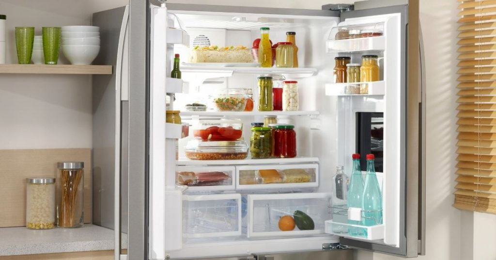 Small, best fridge freezer under £500 opened up with food and condiments inside - Clean and Tidy living