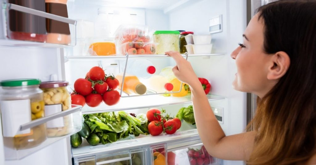 Woman looking at the best fridge freezer under £500 in the UK - Clean and Tidy living