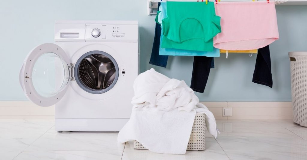 Washing Machine on a Floor with Laundry - How Much Does a Washing Machine Weigh - Clean and Tidy Living