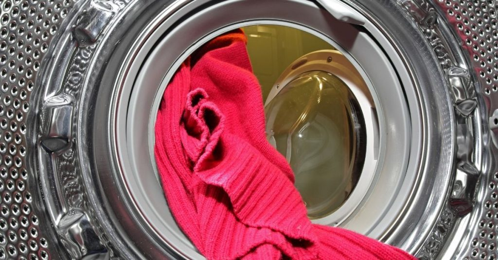 A jumper in the washing machine with the best wool detergent - Clean and Tidy Living